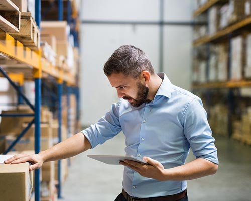 man wearing a blue shirt checking inventory in a warehouse